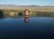 Man with eyes closed in calm lake against sky - CAVF40927