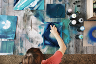 Overhead view of artist spraying paint on cardboard at table - CAVF40966