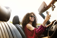 Happy woman clicking selfie while driving car against clear sky - CAVF41110