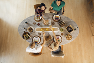 Overhead view of male and female friends toasting drinks at dining table - CAVF41143