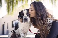 Loving woman kissing dog against building - CAVF41493