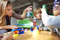 Teacher and students doing science experiment at table in preschool - CAVF41538