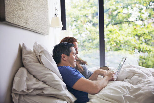 Side view of couple using tablet computer while lying on bed at home - CAVF41556
