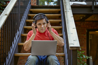 Man listening music through headphones from laptop computer while sitting on steps at yard - CAVF41580