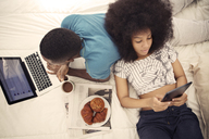 Couple having croissants and using technology while resting on bed at home - CAVF41589