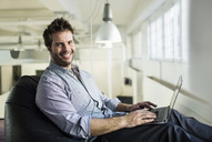 Portrait of smiling businessman using laptop while sitting on bean bag in office - MASF04678