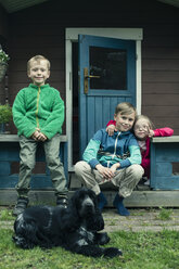 Portrait of siblings with dog sitting on porch - MASF04684