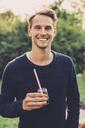 Portrait of happy man holding elderflower drink on roof garden - MASF04696