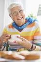 Portrait of happy senior woman having coffee at nursing home - MASF04708