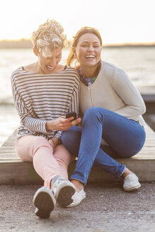 Portrait of happy woman sitting with female friend using mobile phone on pier - MASF04717