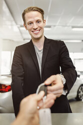 Portrait of happy man receiving keys from saleswoman in car dealership - MASF04735