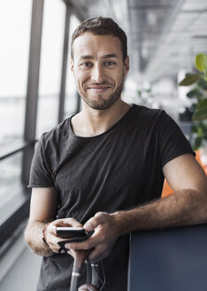 Portrait of smiling businessman holding mobile phone while leaning on cubicle in office - MASF04738