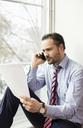 Serious mid adult businessman reading document while on call at office - MASF04741