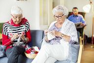Senior women knitting while man reading book in background at nursing home - MASF04765