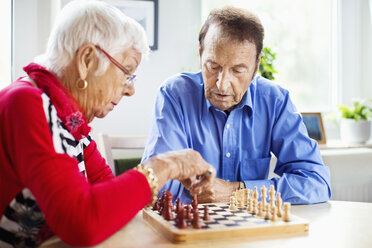 Senior couple playing chess at table in nursing home - MASF04768