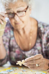Senior woman solving jigsaw puzzle at table in nursing home - MASF04771