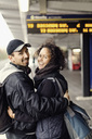 Side view portrait of happy couple with arms around on subway platform - MASF04789