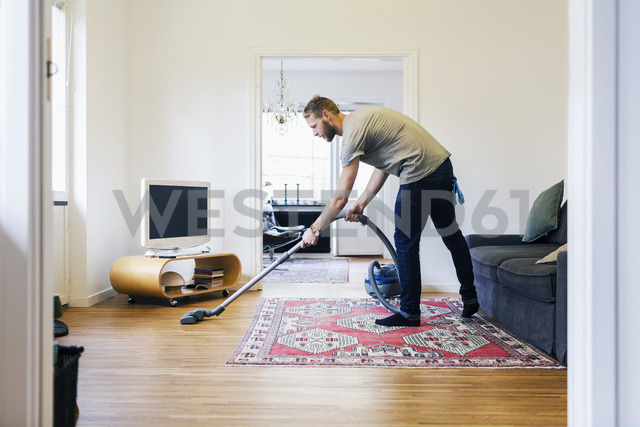 Side view of man vacuuming hardwood floor - MASF04792 - Maskot ./Westend61