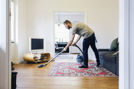 Side view of man vacuuming hardwood floor - MASF04792