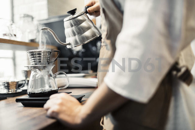Side view midsection of barista pouring boiling water in coffee filter - MASF04795 - Maskot ./Westend61