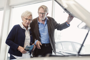 Senior couple examining car engine in showroom - MASF04798