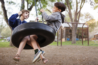 Side view of siblings sitting on tire swing at park - CAVF41698