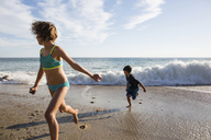 Girl and boy running from rushing waves at beach - CAVF41737