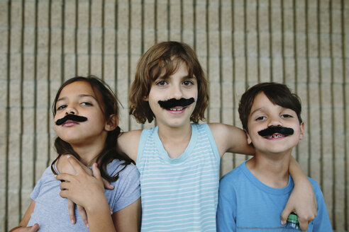 Portrait of happy siblings with artificial mustache against wall - CAVF41761