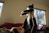 Girl playing with cat while relaxing on bed at home - CAVF41764