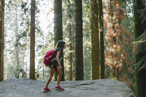 Girl with backpack walking on rock in forest - CAVF41776