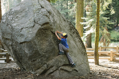 Full length of playful boy climbing rock in forest - CAVF41779
