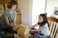 Sisters making gingerbread house at home - CAVF41782