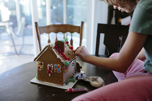 Girl decorating gingerbread house on table at home - CAVF41785