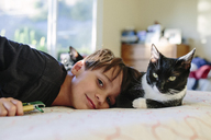 Portrait of boy and cat relaxing on bed at home - CAVF41794