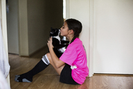 Girl kissing cat while sitting on floor at home - CAVF41797