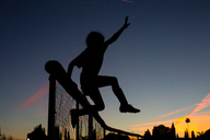 Silhouette sporty girl jumping over fence during dusk against sky - CAVF41830