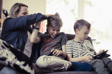 Playful mother pulling son's hair besides boy using digital tablet at home - MASF04818