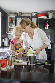 Mother and daughter preparing food in kitchen - MASF04824