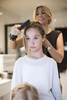 Mother combing daughter's hair at home - MASF04827