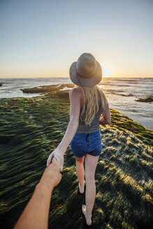 Cropped hand of man holding girlfriend's hand while walking on grass at beach during sunset - CAVF41892