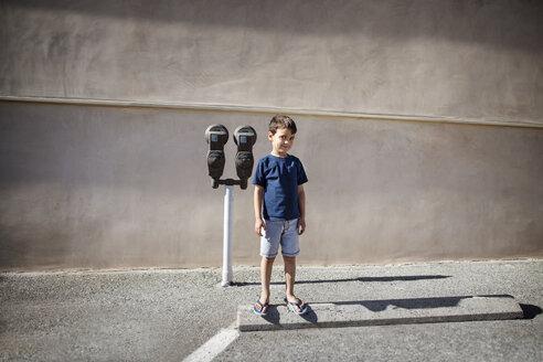 Boy standing against binoculars on road against wall - CAVF41970