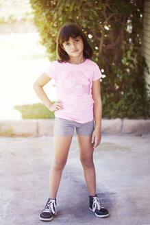 Portrait of confident girl standing on floor against trees - CAVF41997