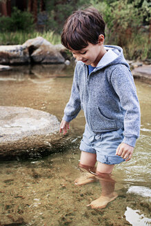 Happy boy standing in water at stream - CAVF42009