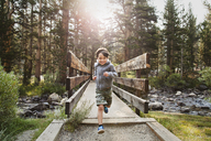 Portrait of boy running over wooden bridge against trees in forest - CAVF42051
