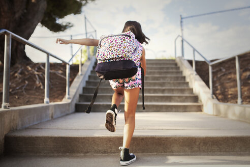 Rear view of girl climbing staircase against sky - CAVF42057