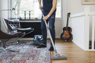 Low section of man vacuuming floor at home - MASF04872
