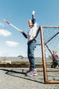 Low angle view of successful girl holding hockey stick against blue sky - MASF04887
