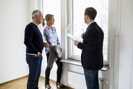 Male real estate agent discussing with couple at home - MASF04893