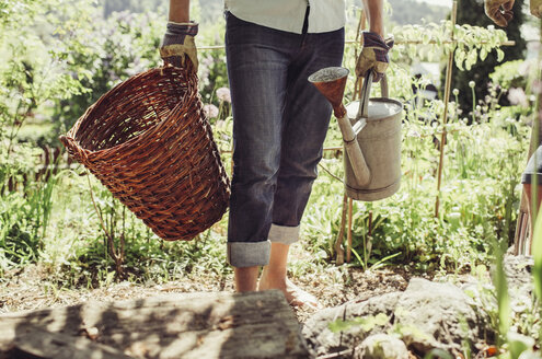 Midsection of man carrying wicker basket and watering can at yard - MASF04899