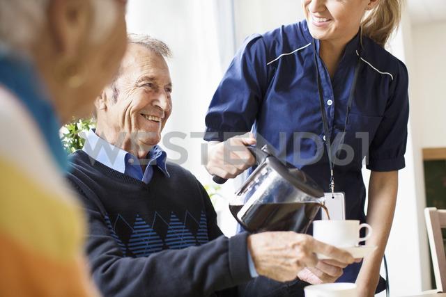 Midsection of happy female caretaker serving black coffee to senior man at nursing home - MASF04902